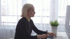 Η νέα γυναίκα χρησιμοποιεί μια γραφική ταμπλέτα και stylus για να εργαστεί πίσω από μια σύγχρονη οθόνη υπολογιστή απόθεμα βίντεο