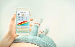 Η νέα γυναίκα χρησιμοποιεί μια ικανότητα app στο smartphone της Στοκ Φωτογραφία