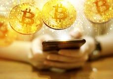 Η νέα γυναίκα χρησιμοποιεί το κινητό τηλέφωνο με το χρυσό bitcoin στοκ εικόνα