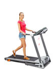 Η νέα γυναίκα χρησιμοποιεί treadmill. Στοκ Φωτογραφία