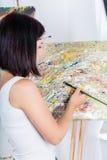 Η νέα γυναίκα χρωματίζει μια εικόνα Στοκ Εικόνες