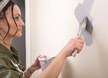 Η νέα γυναίκα χρωματίζει τον τοίχο με τη βούρτσα στο λουτρό Στοκ φωτογραφίες με δικαίωμα ελεύθερης χρήσης
