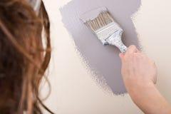 Η νέα γυναίκα χρωματίζει τον τοίχο με τη βούρτσα στο λουτρό Στοκ φωτογραφία με δικαίωμα ελεύθερης χρήσης