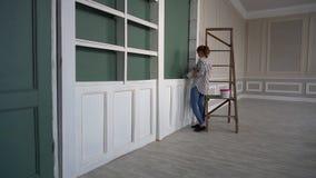 Η νέα γυναίκα χρωματίζει τον τοίχο στη σκούρο πράσινο χρησιμοποιώντας βούρτσα απόθεμα βίντεο