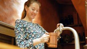 Η νέα γυναίκα χύνει την μπύρα από μια βρύση σε μια ξύλινη κούπα Μια αρκετά καφετής-μαλλιαρή γυναίκα κάνει την εργασία της και χαρ απόθεμα βίντεο