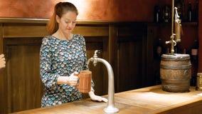 Η νέα γυναίκα χύνει την μπύρα από μια βρύση σε μια ξύλινη κούπα Η αρκετά καφετής-μαλλιαρή γυναίκα κάνει την εργασία της και χαριτ απόθεμα βίντεο