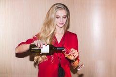 Η νέα γυναίκα χύνει το κρασί σε ένα ποτήρι Στοκ Εικόνες