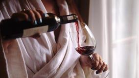 Η νέα γυναίκα χύνει το μπουκάλι του κόκκινου κρασιού σε ένα γυαλί Κορίτσι που μένει κοντά στο παράθυρο μπαλκονιών που ντύνεται σε απόθεμα βίντεο