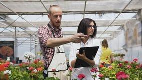 Η νέα γυναίκα ως αγορές πελατών στο κατάστημα ανθοκόμων, αγορά ανθίζει για την κηπουρική Άνθρωποι στο ανθοπωλείο, ώθηση πελατών φιλμ μικρού μήκους