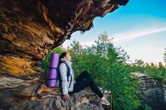 Η νέα γυναίκα backpacker απολαμβάνει τη θέα στην αιχμή βουνών Στοκ φωτογραφία με δικαίωμα ελεύθερης χρήσης