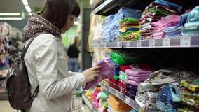 Η νέα γυναίκα brunette επιλέγει και αγοράζει τις πετσέτες υφασμάτων στην υπεραγορά απόθεμα βίντεο