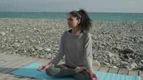 Η νέα γυναίκα brunette κάθεται στη θέση λωτού στην ακροθαλασσιά και απόθεμα βίντεο