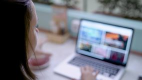 Η νέα γυναίκα brunette κοιτάζει βιαστικά την περιοχή, ψωνίζοντας on-line με το σημειωματάριο και τον καφέ κατανάλωσης στο σαφές δ φιλμ μικρού μήκους