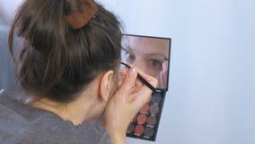 Η νέα γυναίκα brunette μαδά τα φρύδια της με τα τσιμπιδάκια μπροστά από τον καθρέφτη στο σπίτι απόθεμα βίντεο