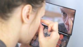 Η νέα γυναίκα brunette μαδά τα φρύδια της με τα τσιμπιδάκια μπροστά από τον καθρέφτη στο σπίτι φιλμ μικρού μήκους