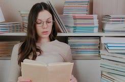Η νέα γυναίκα brunette στα γυαλιά διαβάζει ένα βιβλίο μεγαλοφώνως καθμένος μεταξύ των βιβλίων στοκ φωτογραφία με δικαίωμα ελεύθερης χρήσης