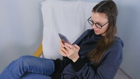 Η νέα γυναίκα brunette στα γυαλιά παίζει το παιχνίδι στην κινητή τηλεφωνική συνεδρίαση στην πολυθρόνα απόθεμα βίντεο