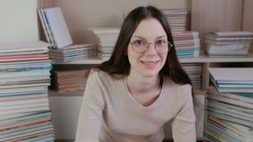 Η νέα γυναίκα brunette στα γυαλιά σκέφτεται και χαμογελά απόθεμα βίντεο