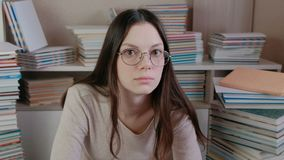 Η νέα γυναίκα brunette στα γυαλιά σκέφτεται απόθεμα βίντεο