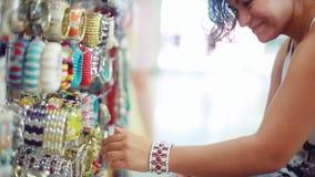 Η νέα γυναίκα brunette χαμόγελων επιλέγει bijouterie στο κατάστημα κοσμήματος στο θολωμένο bokeh υπόβαθρο 1920x1080 απόθεμα βίντεο