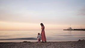 Η νέα γυναίκα mom στο φόρεμα περπατά κατά μήκος της ακτής στο ηλιοβασίλεμα με μια μικρή κόρη απόθεμα βίντεο