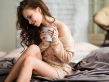 Η νέα γυναίκα smiley χαλαρώνει στο σπίτι και πίνει τον ευώδη καφέ Στοκ Εικόνες