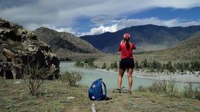 Η νέα γυναίκα torist στέκεται στην άκρη του βουνού και παίρνει το φυσικό τοπίο φωτογραφιών Πίσω άποψη, ολισθαίνων ρυθμιστής φιλμ μικρού μήκους