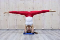 Η νέα ελκυστική έννοια γιόγκας άσκησης γυναικών γιόγκη, που στέκεται στην παραλλαγή της άσκησης Pincha Mayurasana, handstand θέτε στοκ εικόνα