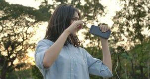 Η νέα ελκυστική ασιατική γυναίκα ακούει τη μουσική με το τηλέφωνο και τα ακουστικά απολαμβάνοντας τους υγιείς χορούς σε ένα θεριν απόθεμα βίντεο