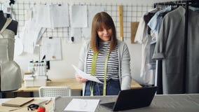 Η νέα ελκυστική γυναίκα επιλέγει τα σκίτσα για τη νέα επίδειξη μόδας και χρησιμοποιεί το lap-top στο κατάστημα ραφτών της ` s δημ φιλμ μικρού μήκους