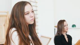 Η νέα ελκυστική γυναίκα κάθεται πίσω από easel στενό τον επάνω φιλμ μικρού μήκους