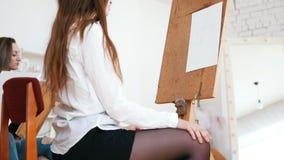 Η νέα ελκυστική γυναίκα κάθεται πίσω από easel απόθεμα βίντεο