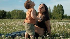 Η νέα ελκυστική γυναίκα και ο γιος της γελούν βρισκόμενος τη χλόη στο πάρκο φιλμ μικρού μήκους