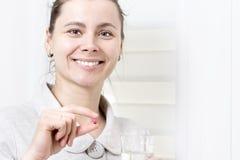 Η νέα ελκυστική γυναίκα κρατά στο χάπι χεριών και το γυαλί καθαρού της Στοκ εικόνα με δικαίωμα ελεύθερης χρήσης