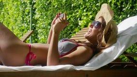 Η νέα ελκυστική γυναίκα που φορά τα γυαλιά ηλίου, το καπέλο και ένα μπικίνι χαλαρώνει σε μια καρέκλα γεφυρών παράλληλα με μια λίμ φιλμ μικρού μήκους