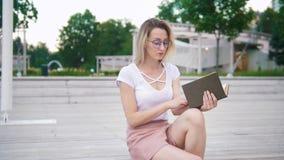 Η νέα ελκυστική γυναίκα στα γυαλιά διαβάζει τη συνεδρίαση βιβλίων στο πάρκο απόθεμα βίντεο
