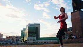 Η νέα ελκυστική γυναίκα στο pointe πηδά στο χορευτικό βήμα μπαλέτου σε ένα τετράγωνο με ένα μνημείο απόθεμα βίντεο