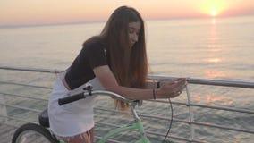 Η νέα ελκυστική γυναίκα χρησιμοποιεί ένα smartphone και ένα οδηγώντας εκλεκτής ποιότητας ποδήλατο κοντά στη θάλασσα κατά τη διάρκ φιλμ μικρού μήκους