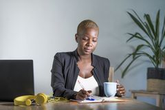 Η νέα ελκυστική και επιτυχής μαύρη αμερικανική γυναίκα afro στην εργασία επιχειρησιακών σακακιών σοβαρή στη λήψη lap-top γραφείων Στοκ Φωτογραφία