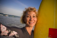 Η νέα ελκυστική και ευτυχής ξανθή γυναίκα surfer στον πίνακα κυματωγών εκμετάλλευσης μαγιό στην παραλία που παίρνει την αυτοπροσω στοκ εικόνα