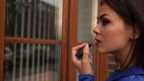 Η νέα ελκυστική μοντέρνη γυναίκα χρωματίζει τα χείλια της με το κραγιόν εξετάζοντας την αντανάκλαση στο παράθυρο έξω φιλμ μικρού μήκους