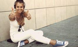 Η νέα ελκυστική μουσική ακούσματος κοριτσιών με το ακουστικό και παρουσιάζει τ Στοκ Εικόνες