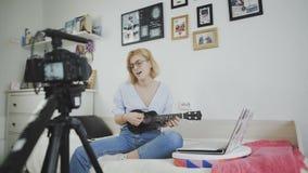 Η νέα ελκυστική μόδα κοριτσιών blogger καταγράφει το βίντεο με τη κάμερα, τραγουδά και παίζει στην κιθάρα φιλμ μικρού μήκους