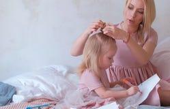 Η νέα ελκυστική ξανθή γυναίκα πλέκει την τρίχα σε την λίγη γοητευτική κόρη στα ρόδινα φορέματα ενώ αυτή που χρωματίζει με αισθητό Στοκ Εικόνα