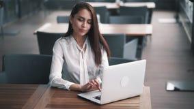 Η νέα επιτυχής επιχειρηματίας κάθεται στο θερινό καφέ, εργάζεται στο lap-top, σε αργή κίνηση φιλμ μικρού μήκους