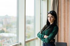 Η νέα, επιτυχής επιχειρησιακή γυναίκα με τη μαύρη τρίχα και τα όπλα που διασχίζονται υπερασπίζονται το παράθυρο στοκ εικόνες με δικαίωμα ελεύθερης χρήσης