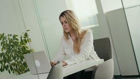 Η νέα επιχειρηματίας εργάζεται στον υπολογιστή σε ένα φωτεινό γραφείο φιλμ μικρού μήκους