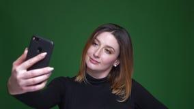 Η νέα επιχειρηματίας με την τρίχα κάστανων κάνει τις όμορφες selfie-φωτογραφίες στο πράσινο υπόβαθρο φιλμ μικρού μήκους