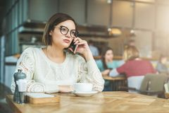 Η νέα επιχειρηματίας στα γυαλιά και το άσπρο πουλόβερ κάθεται στον καφέ στον ξύλινο πίνακα και μιλά στο τηλέφωνο κυττάρων Στοκ φωτογραφία με δικαίωμα ελεύθερης χρήσης