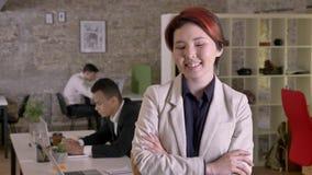Η νέα επιχειρησιακή ασιατική γυναίκα με τα διασχισμένα χέρια που φαίνεται κεκλεισμένων των θυρών στο σύγχρονο γραφείο, χαμογελώντ απόθεμα βίντεο